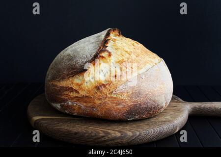 Sourdough bread on wooden cut board on black background - Stock Photo