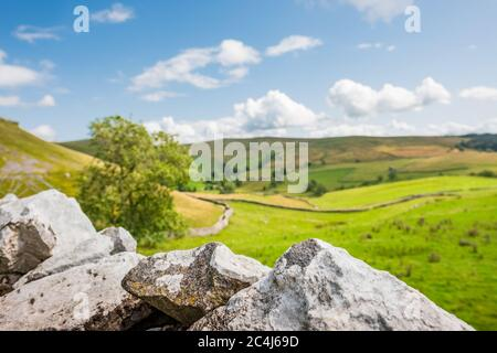 Picturesque view of the stunning Yorkshire Dales as seen from a stone wall. In focus barbed wire is seen in the foreground to prevent trespassers. - Stock Photo