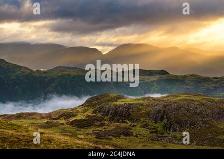 Beautiful Golden Rays Of Sunlight Breaking Through Clouds On A Misty Morning In The English Lake District. - Stock Photo