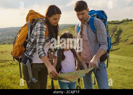 Family with backpacks look at the map are guided on a hiking trip in nature.