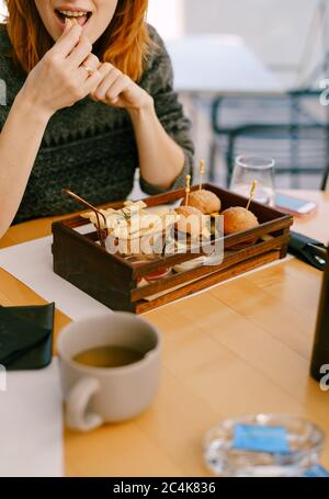 The girl in the restaurant eats mini burgers and fries. - Stock Photo