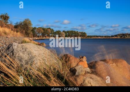 Beach section on the island of Ruegen on the Baltic Sea. Blue horizon in autumn sunshine. Stones and grasses in the foreground. Trees on the coastline