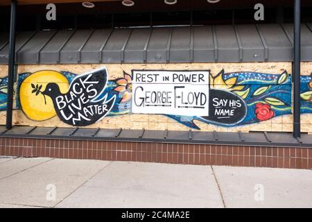George Floyd 'Rest in Power' 'Black Lives Matter' 'Say his Name' painted on plywood window. protectors. Minneapolis Minnesota MN USA - Stock Photo