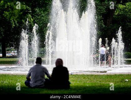 Berlin, Germany. 28th June, 2020. Two people sit in Treptower Park in the grass in front of a fountain. Credit: Fabian Sommer/dpa/Alamy Live News - Stock Photo