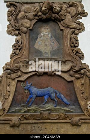 The scrollwork of a Baroque double cartouche encloses a blue-painted relief of a fox and a faded painting of the Carmelite Infant or Child Jesus statue above the doorway, dated 1664, of At The Blue Fox (U na Modré Lisky) on Kampa Island, Prague, Czech Republic / Czechia.   The Blue Fox is among at least 300 ancient properties in the city to retain traditional house signs or name plaques.  The house at Na Kampě 498/1 is now occupied by the Embassy of the Republic of Estonia.