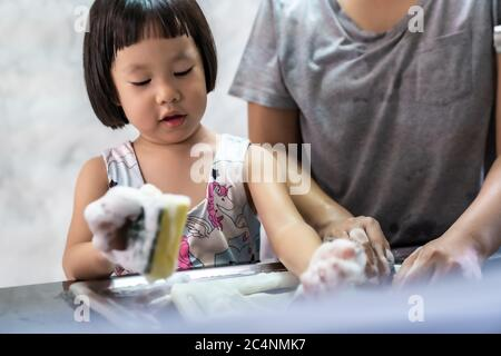 Asian girl washing dish and tableware with her mom, housework for child make executive function for kid. Houseworking for kid lifstyle and family conc