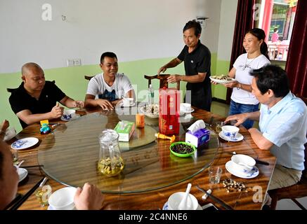 (200628) -- NANCHANG, June 28, 2020 (Xinhua) -- Zhu Yicai (3rd L) serves guests at his farmhouse in the Poyang Lake scenic area in Yugan County, east China's Jiangxi Province, June 16, 2020. Zhu Yicai gave up his fishing business in 2012 due to the worsening aquatic environment in the Poyang Lake. In 2018, Zhu was running a family farm when he noticed that lots of tourists came to the lake to watch migratory birds. Zhu then captured the business opportunity and opened a 1,800-square-meter farmhouse, which can accommodate more than 200 people dining at the same time. China began a 10-year fishi Stock Photo