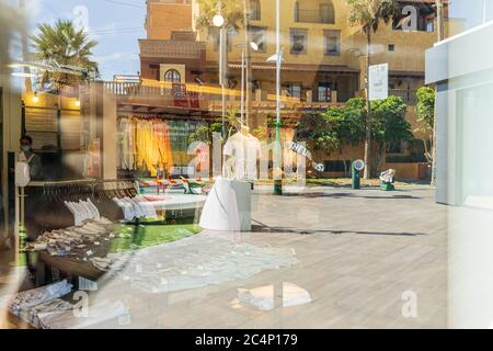 Reflections in windows along the Avenida de Las Américas, nicknamed the Golden Mile, a shoppers paradise in Playa de Las Americas, in a time of practically zero tourism with hotels still closed, most shops and restaurants shut, a few that are open struggling to attract some local residents. Playa de Las Americas, Tenerife, Canary Islands, Spain. 27 June 2020. - Stock Photo