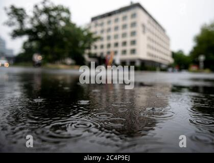 Berlin, Germany. 28th June, 2020. Raindrops fall into a puddle in Berlin Mitte. Credit: Fabian Sommer/dpa/Alamy Live News - Stock Photo