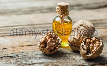 Walnut oil in glass of bottle, whole big peeled walnut kernel with thin shell on wooden background. healthy food for brain. Fresh walnuts background - Stock Photo