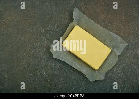 Close up open fresh yellow hard stick butter in paper on grunge table surface, elevated top view, directly above - Stock Photo