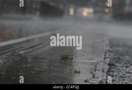 Berlin, Germany. 28th June, 2020. A short but heavy rain showers over Berlin at Prenzlauer Allee. Credit: Annette Riedl/dpa/Alamy Live News - Stock Photo