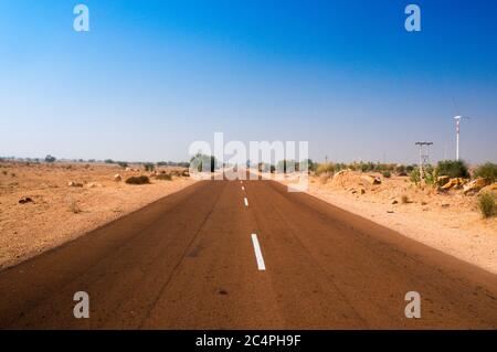 Narrow highway road with barren desert on both sides shot in Rajasthan India - Stock Photo