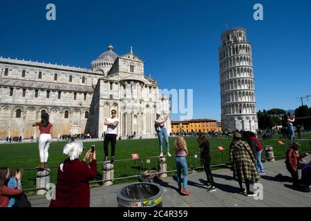 Tourists pose for pictures in front of The Leaning Tower of Pisa, campanile for the Pisa cathedral and UNESCO world heritage site, Pisa, Tuscany, Ital - Stock Photo