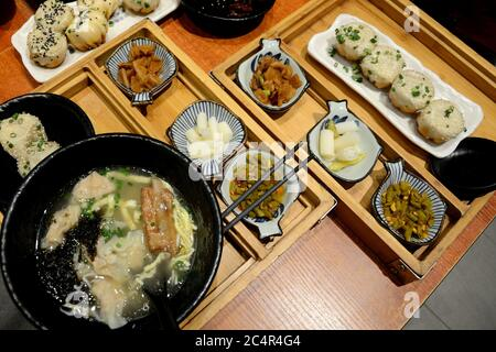 Typical Chinese food on tablechi in Guangzhou, China. Bowl of soup with noodle and ribs, spicy snacks - bean, garlic and Chinese dumplings 'baozi'. - Stock Photo