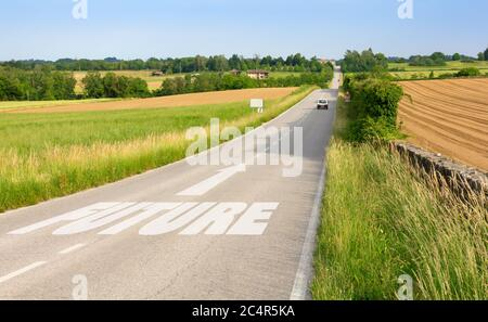 Country road among hills with sign on asphalt indicating the driving direction toward the future - Stock Photo