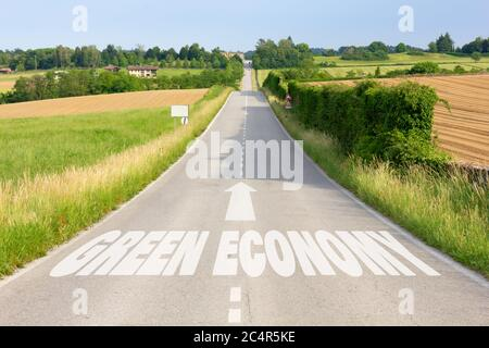 Country road among hills with sign on asphalt indicating the driving direction toward a green economy - Stock Photo