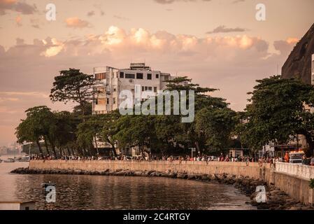 Beautiful view to Urca ocean shore with people socializing by the sunset, Guanabara Bay, Rio de Janeiro, Brazil - Stock Photo