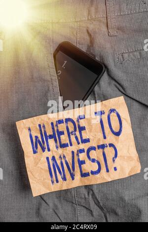 Writing note showing Where To Invest Question. Business concept for fundraising money to start business project startup Smartphone device inside trous - Stock Photo