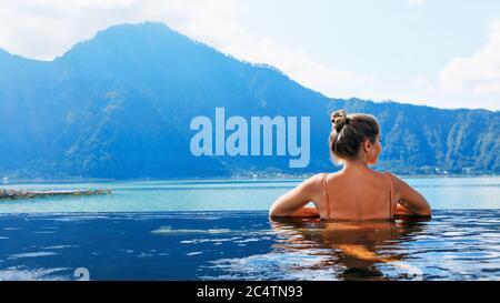 Young woman relax in infinity pool with lake view. Natural hot spring spa under Batur volcano. Travel in Kintamani, Bali. Healthy lifestyle. - Stock Photo