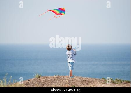 one little kid with flying color kite in air above blue ocean and sky in summer leisure games