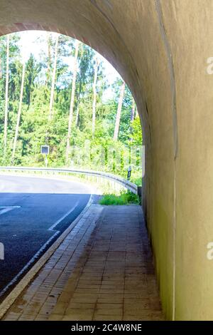 view through a railway tunnel, with focus on the gutter along the road - Stock Photo