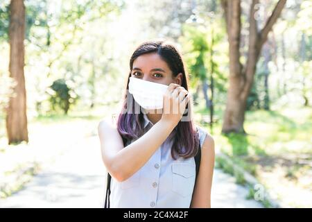 feeling free. young woman alone in park removing medical mask and breathing cheerfully - Stock Photo