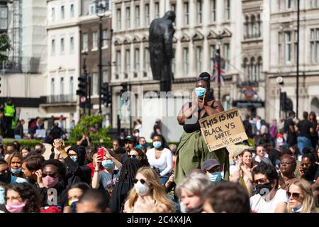 A female protester stands among a crowd clapping during a Black Lives Matter Demonstration, Parliament Square, London, 21 June 2020 - Stock Photo