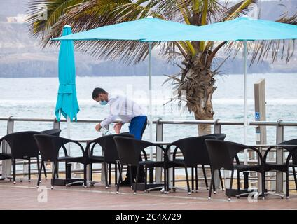 Las Palmas, Gran Canaria, Canary Islands, Spain. 29th June, 2020. A waiter cleans empty restaurant tables overlooking a tourist free city beach in Las Palmas on Gran Canaria. With major tour operators from the UK not due to start flights to gran Canaria until mid July, many hotels remain closed. With the Canary Islands one of the least effected provinces of Spain during the Coronavirus pandemic, locals are keen to see the return of tourists, as around 40% of the Canary Islands population depend on tourism for employment. Credit: Alan Dawson/Alamy Live News. - Stock Photo