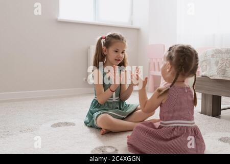 Cute little sisters playing together sitting on the carpet in identical dresses different colors in a room with lots of light