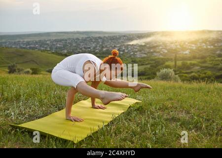 Yoga meditation in nature. Flexible young girl doing yoga on mountain top at sunrise. - Stock Photo