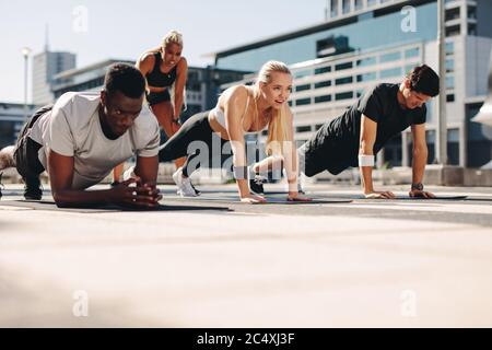 Group of people doing core exercise on fitness mat outdoors. Athletic group training together in the city. - Stock Photo