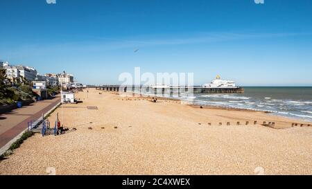 Eastbourne promenade, beach and pier, UK. A bright spring view of the seafront to the popular East Sussex seaside town on the south coast of England. - Stock Photo
