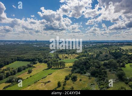 29 June 2020, Hessen, Frankfurt/Main: Clouds are moving in front of a bright blue sky over the Enkheimer Ried, while the skyline of Frankfurt can be seen in the background (aerial view with a drone). According to the meteorologists' forecasts, the coming days will continue to be hot and summery. Photo: Boris Roessler/dpa - Stock Photo