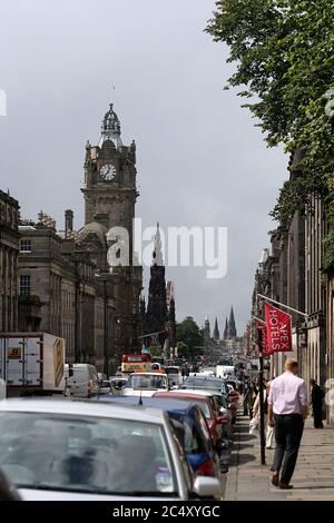 Princes Street, Edinburgh with car traffic, iconic Balmoral Hotel and Scott Monument in the background. Pedestrians and tourists walking on sidewalk. - Stock Photo