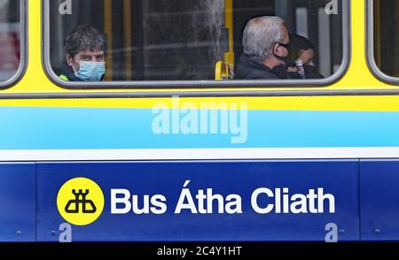 People riding a bus in Dublin wear face coverings, which are now compulsory on public transport, as Ireland enters phase three of Covid-19 lockdown restrictions. - Stock Photo