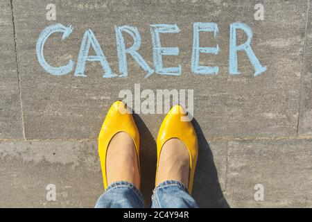 Career concept, top view on woman legs and text written in chalk on gray sidewalk - Stock Photo