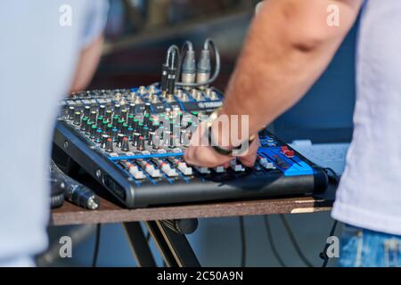 DJ mixer controller. DJ hand control music in open air party. Professional audio equipment for rock concert, night club dance party or wedding. - Stock Photo