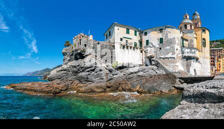 Panorama of medieval fortification and basilica on the rocks in Mediterranean sea under blue sky in small town of Camogli, Liguria, Italy. - Stock Photo