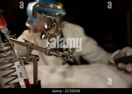 Study of biochemical reactions using tools such as test tubes and syringes to manipulate plasma by a research doctor in Mexico City in the new reality - Stock Photo