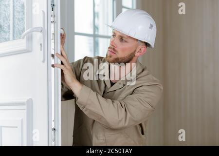 handsome young man installing bay window in a new house - Stock Photo