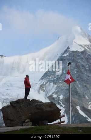 Male tourist looking at beautiful mountains scenery . Man standing on stones near the flagpole with Switzerland flag. Ober Gabelhorn is on background. Wild nature with amazing views. Tourism in Alps.