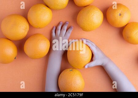 Girl hands holding appetizing fresh oranges, top view. - Stock Photo