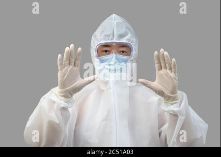 An Asian man wearing protective suit, medical masks, and goggles on a gray background. - Stock Photo