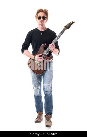 Handsome young red hair rocker stepping forward playing electric guitar. Full length portrait isolated on white background. - Stock Photo