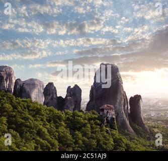 sunset on monastery Agias Varvaras Roussanou on top of rock Meteora, Greece - Stock Photo