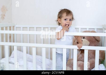 quarantine concept. safety is relative. little cute toddler is standing in the crib and looking at the camera - Stock Photo