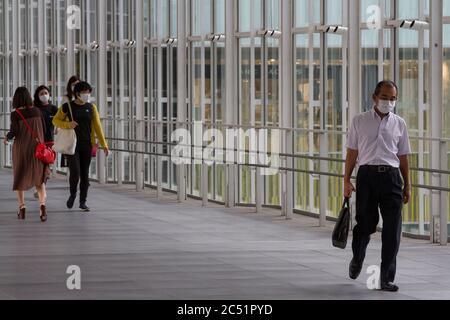 A Japanese salaryman  and women, wearing face masks, walking a covered walkway near Shibuya Hikarie Shibuya, Tokyo, Japan. Tuesday June 23rd 2020 - Stock Photo