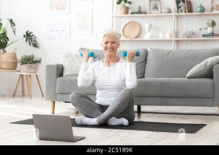 Home Training. Smiling Senior Woman Excercising With Dumbbells In Front Of Laptop - Stock Photo