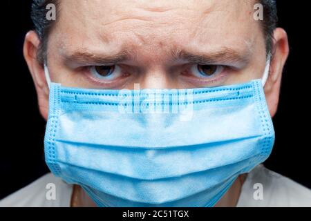 male portrait a face in a medical mask with frowning eyebrows and dissatisfied emotion due to epidemic of the coronavirus stovid virus covid 19, close